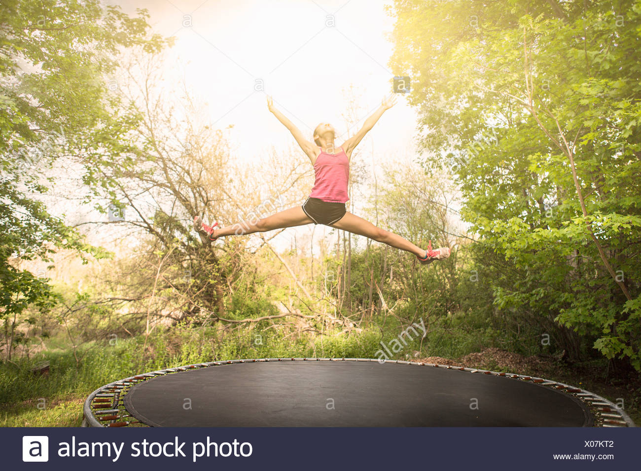 Teenage girl doing star saut sur trampoline, à l'extérieur Photo Stock
