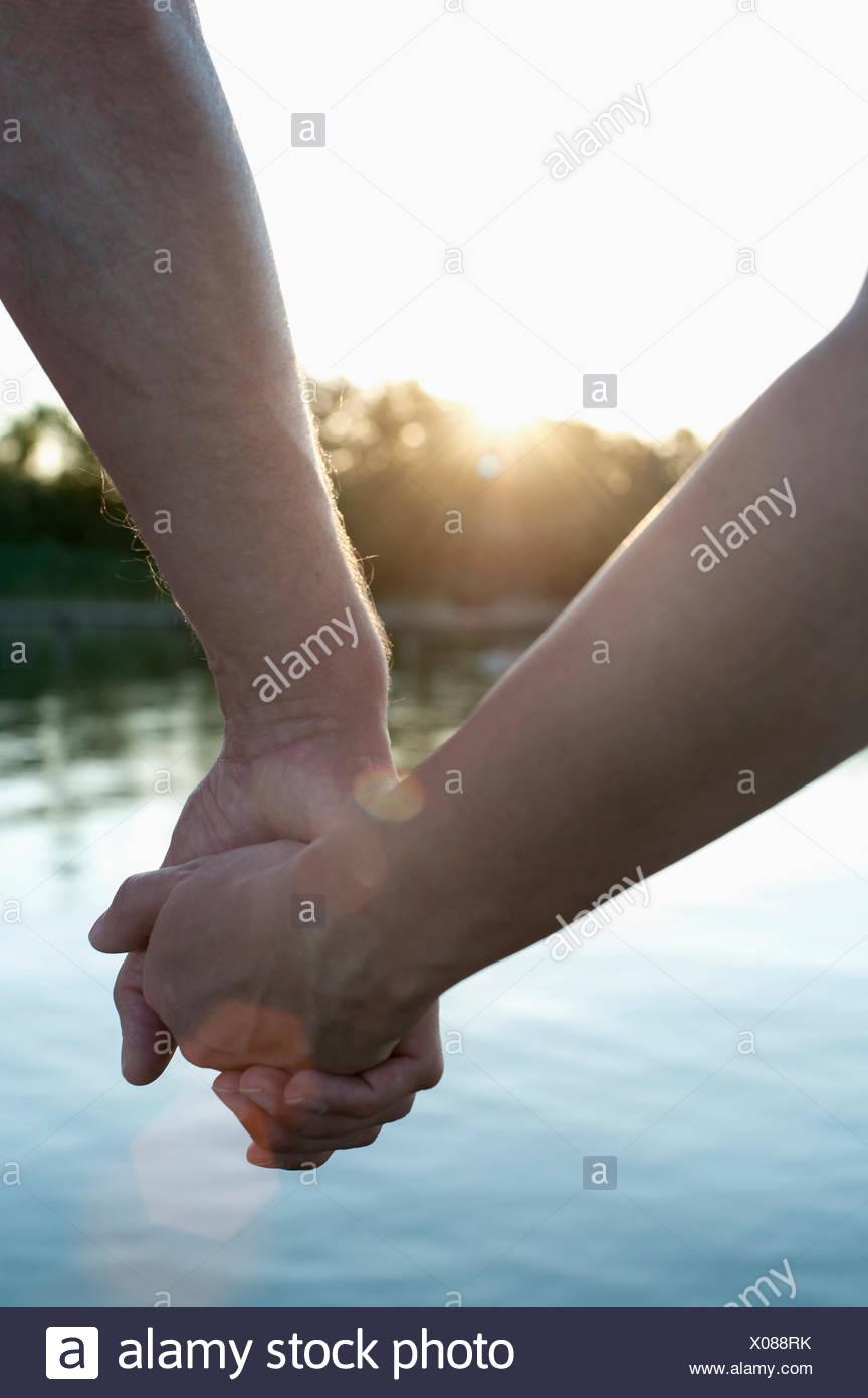 Close-up of couple amoureux se tenant la main pendant le coucher du soleil, Bavière, Allemagne Photo Stock