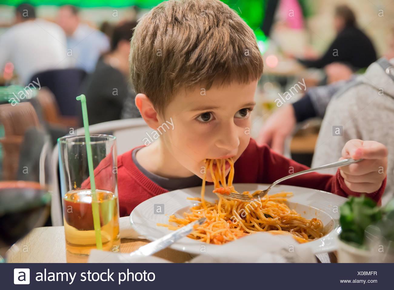 Garçon assis dans un restaurant mange du spaghetti Photo Stock