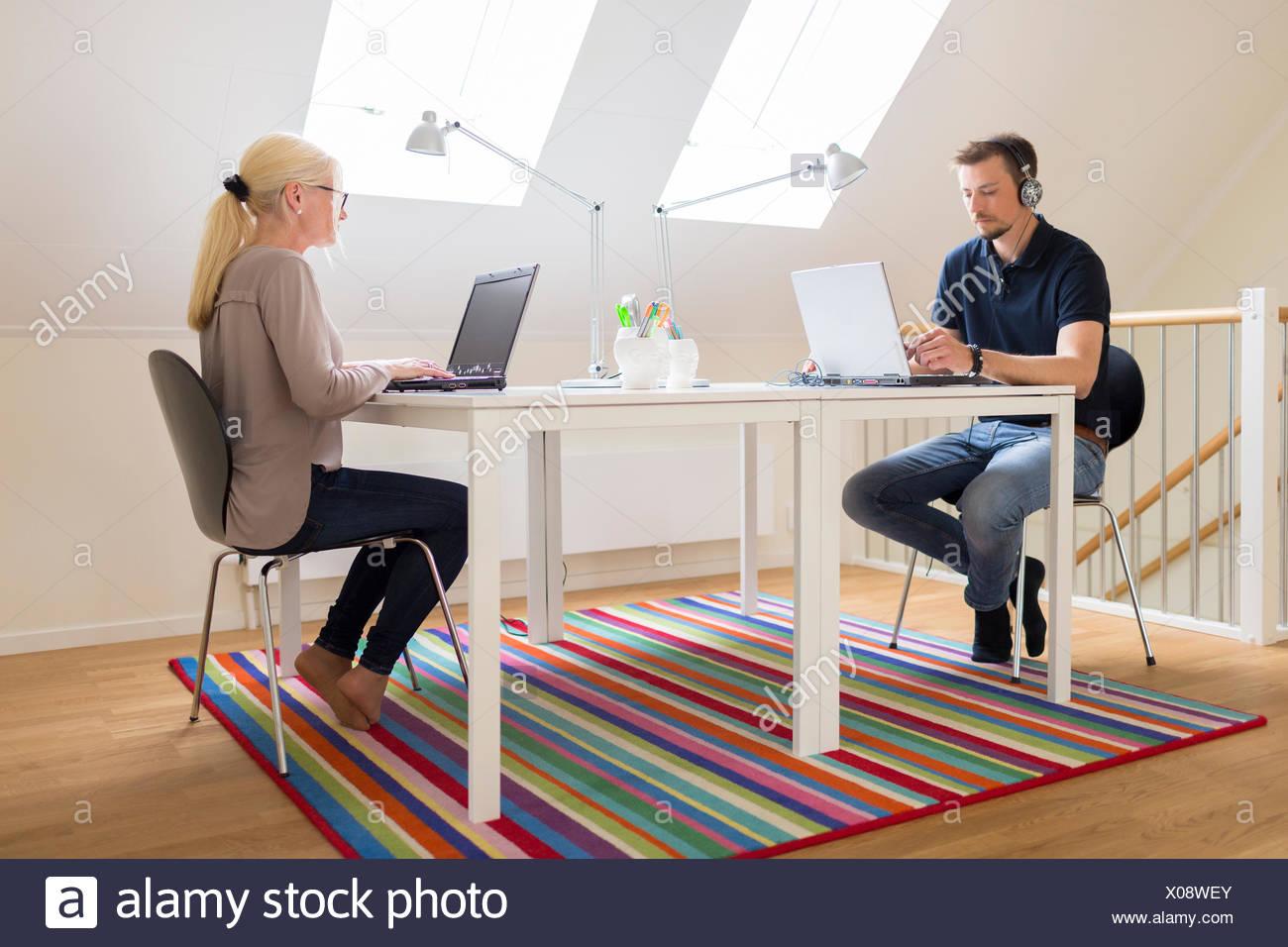La Suède, un couple travaillant à domicile Photo Stock