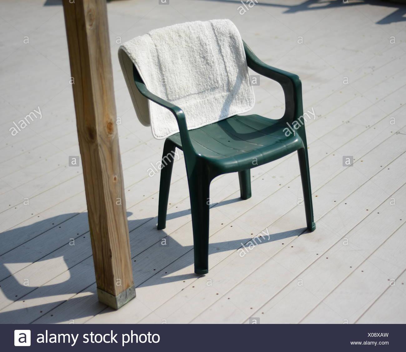 Portrait de serviettes sur la chaise en plastique par Wooden Post Photo Stock