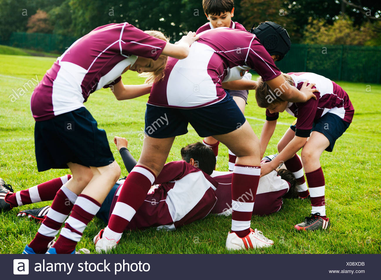 L'équipe de rugby d'écolier adolescents jouant agressivement Photo Stock