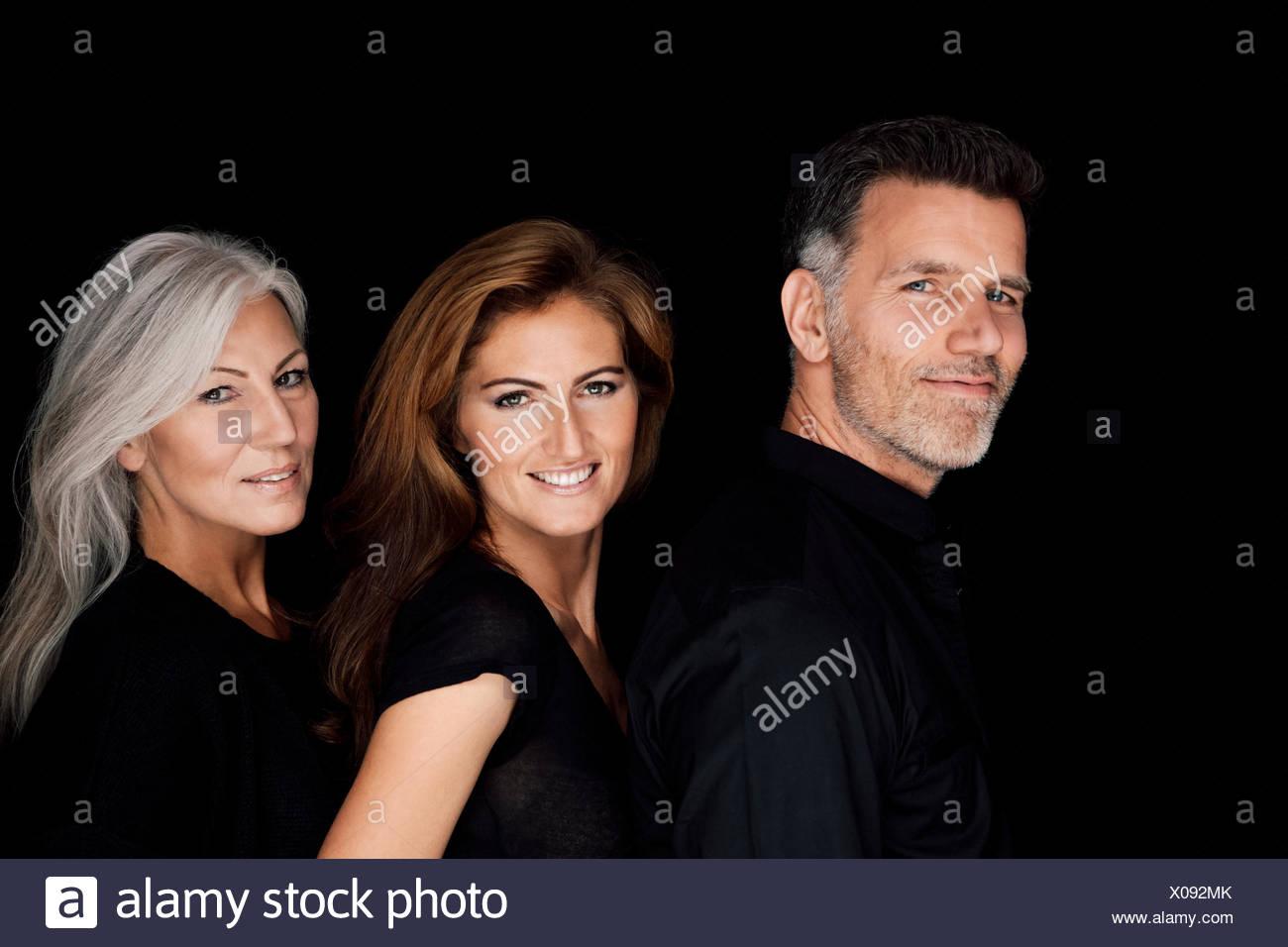 Portrait de trois personnes dans une rangée en face de fond noir Photo Stock