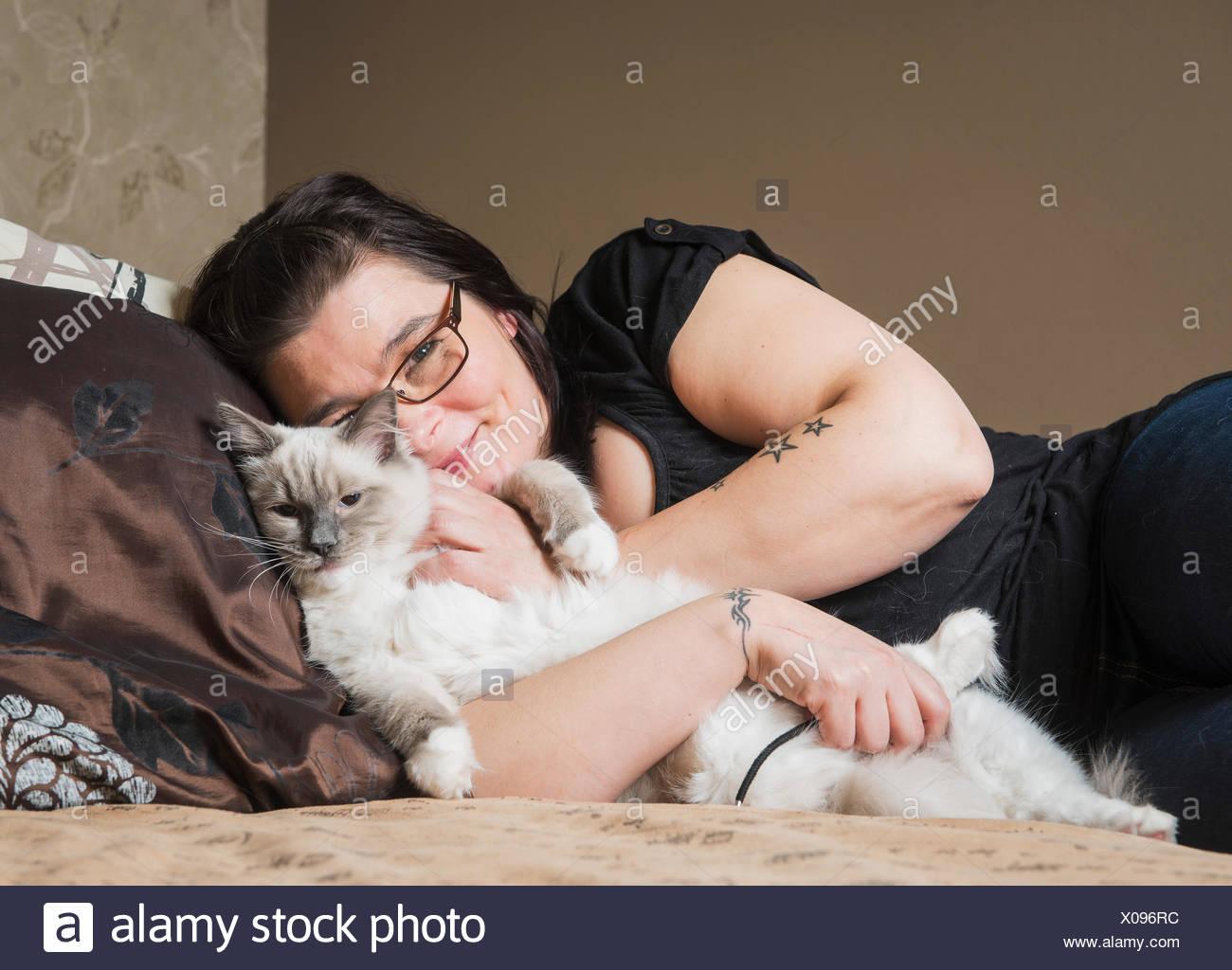 Portrait de chat Ragdoll avec propriétaire, détente sur lit Banque D'Images