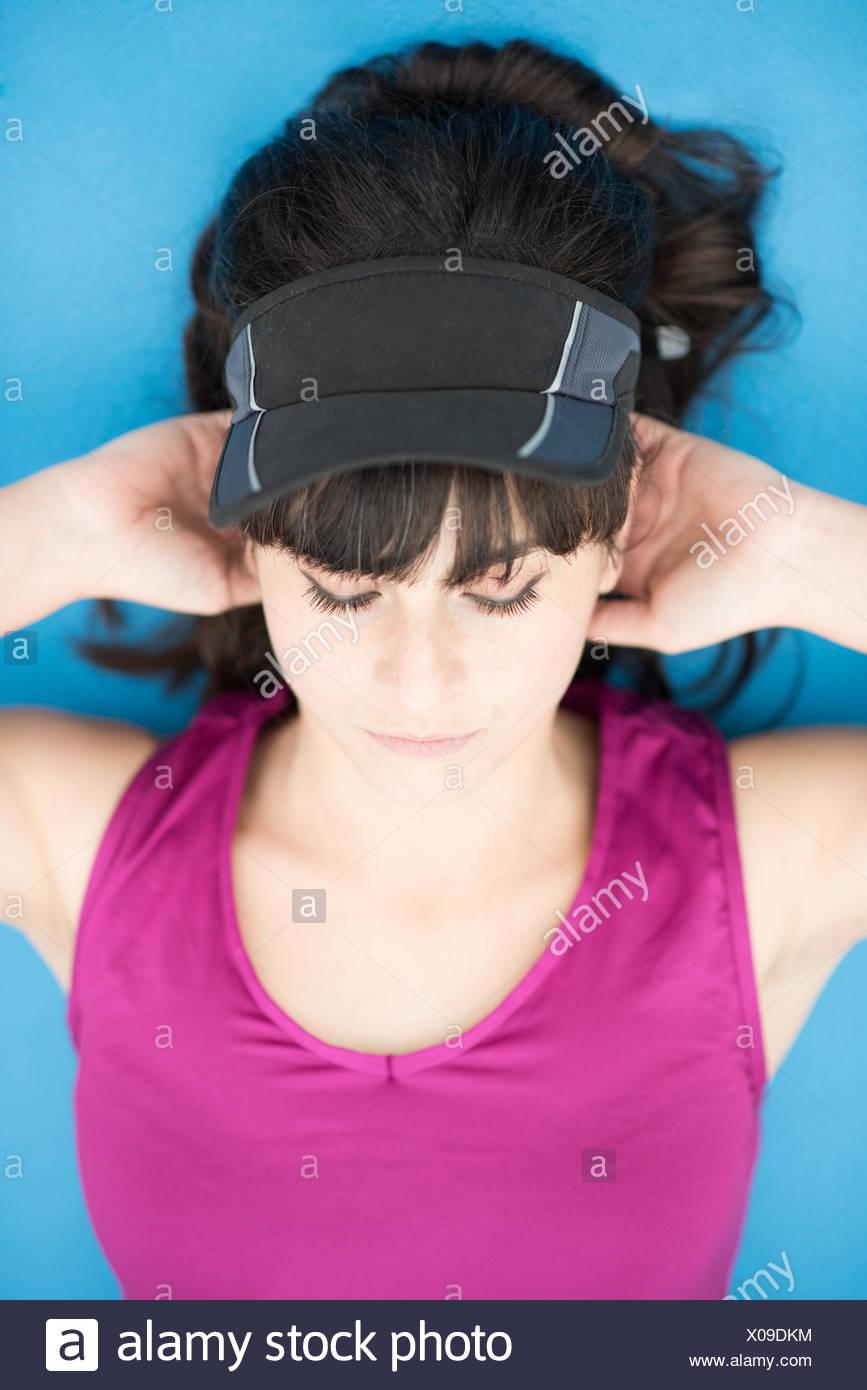 Jeune femme couché l'exercice avec les mains derrière la tête Photo Stock