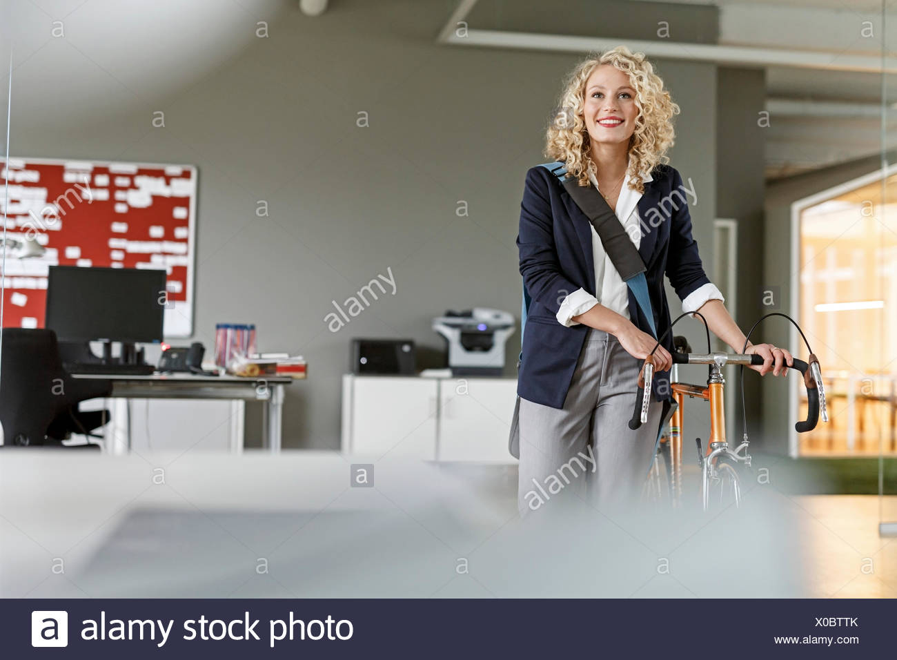 Smiling woman with bicycle in office Photo Stock