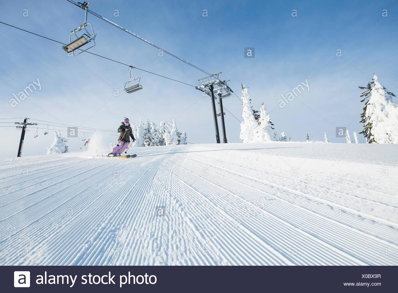 Mid-adult woman sur la pente de ski téléphérique sous Photo Stock