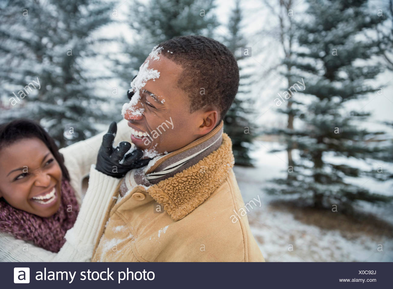 Cheerful couple having snowball fight en hiver Photo Stock