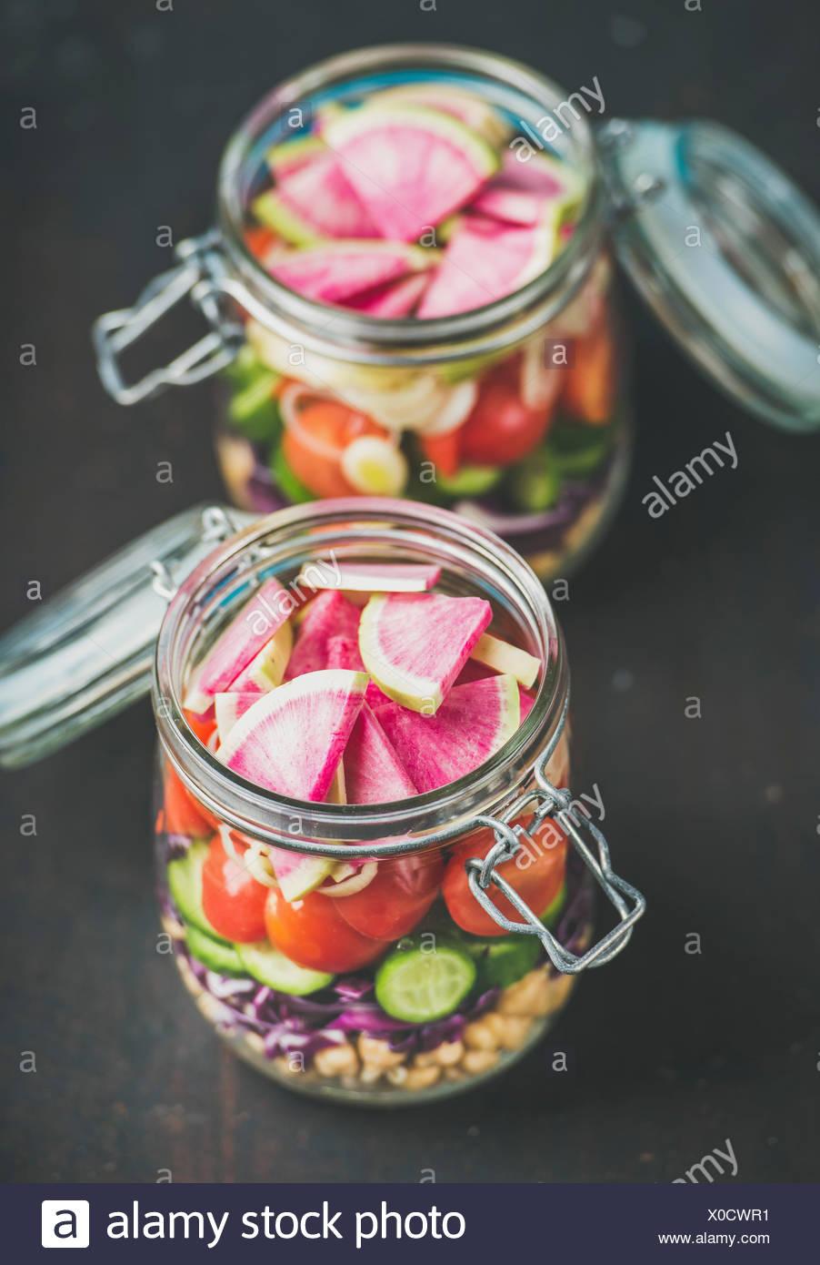 Déjeuner à emporter en bonne santé. Les légumes et les germes de pois chiches salade vegan en couches dans des bocaux en verre sombre sur fond de bois brûlée, selective focus. C Photo Stock