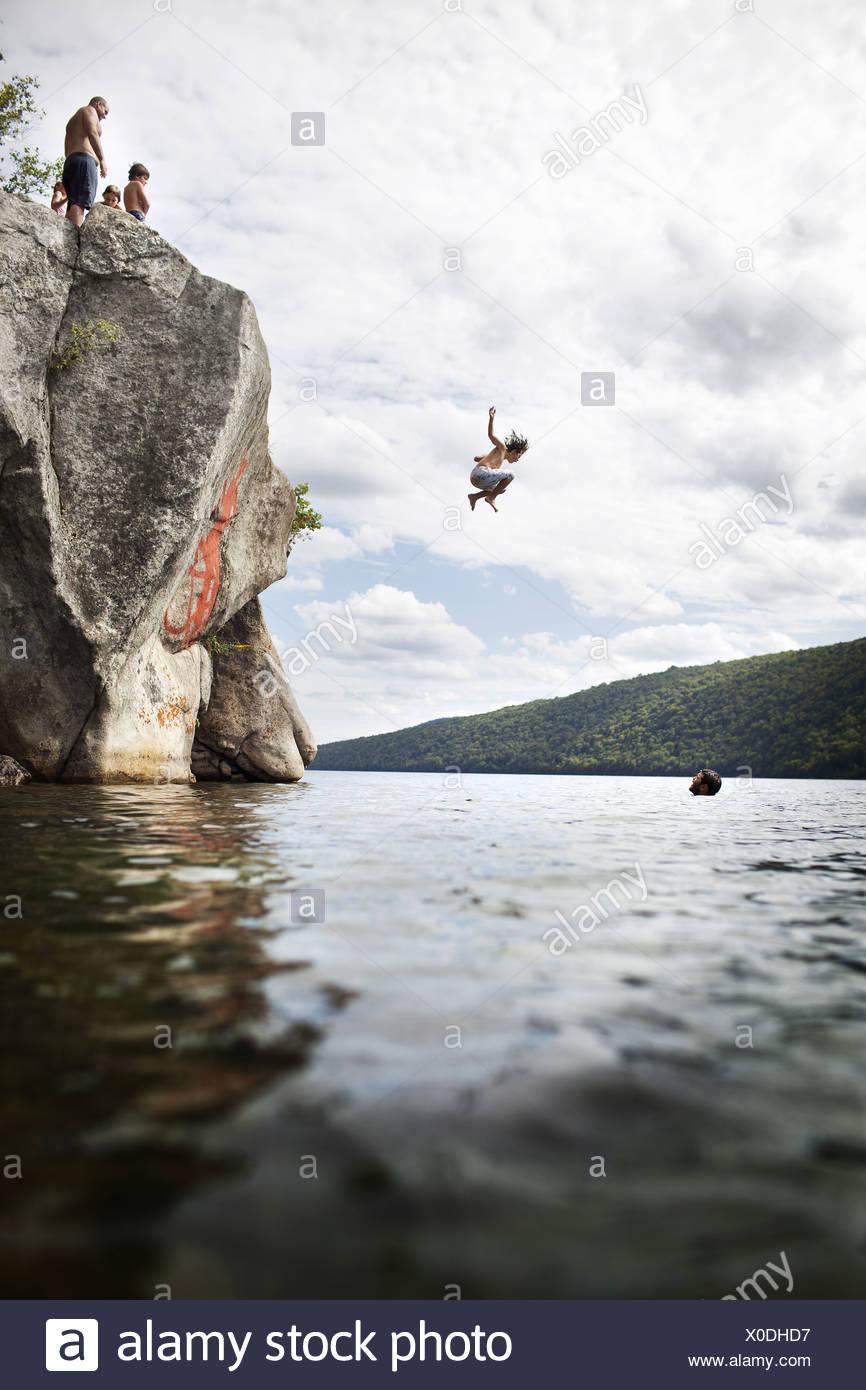 Massachusetts USA groupe de jeunes sautant de Cliff Lake Photo Stock