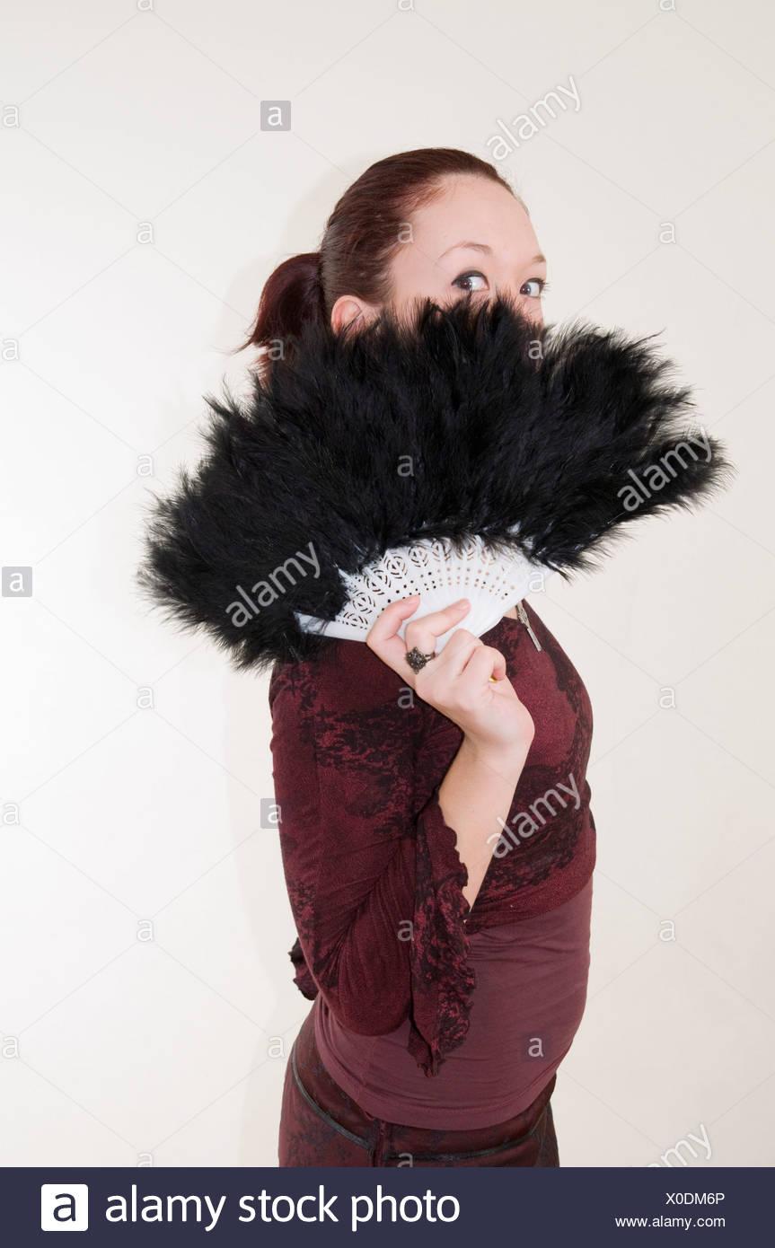 Les jeunes adolescents gothiques se cacher derrière un ventilateur à plumes noir modèle libération disponible Photo Stock