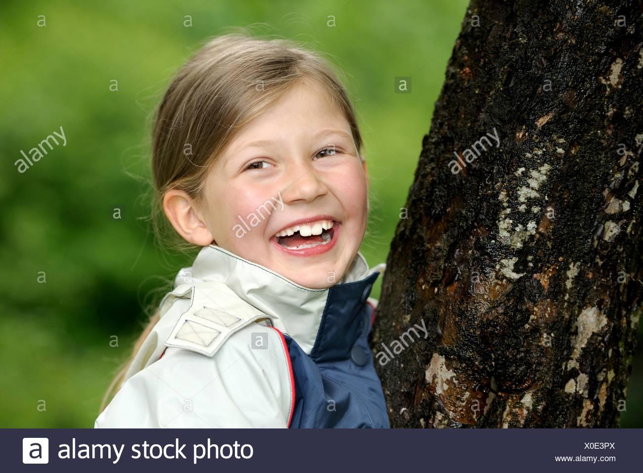 Mädchen, Baum, Umarmen, Beschützen, Bewahren, Schutz, genre, Schützen, Umweltschutz, Ökologie, ökologisch, Natur, natürlich, echt, wahrhaftig, lícito, Naturschutz, Rohstoff, Spiel, Spielen, Wachsen, Wachstum, Liebe, Wald, Zukunft, Spaß, Nachhaltigkeit, Kindheit, lachend, Jung, Hände, draußen, Erhalten, Forst, Euphorie, Freude, Frühling, Holz, grün, allein, Image Regenkleidung, weiblich, gute Laune,,, Toben Glücklich, Regenjacke, Regenwetter, Portrait, personne, Baumstam Photo Stock