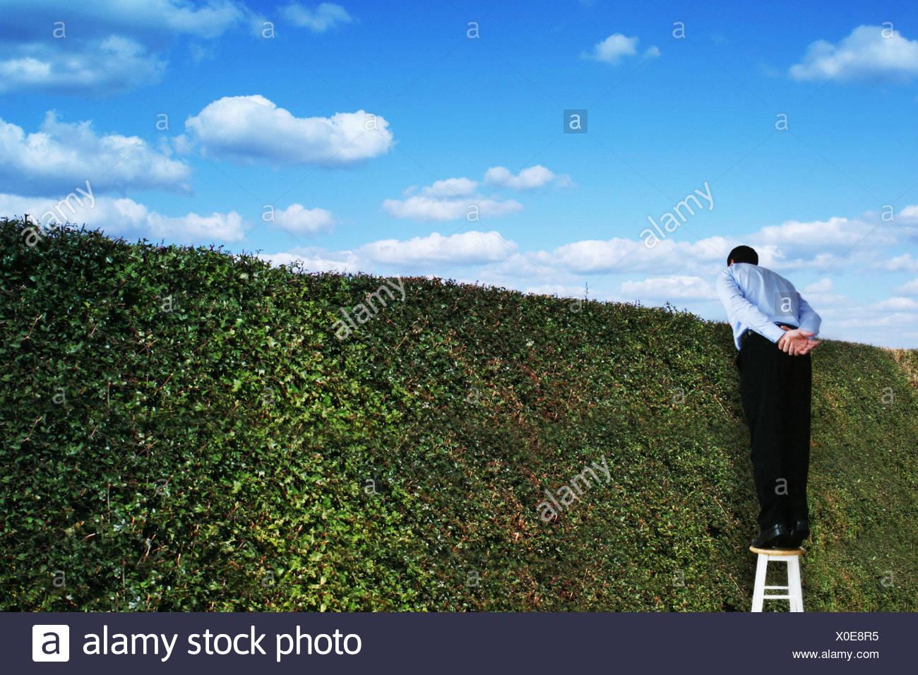 Homme était debout sur un tabouret à la recherche sur une couverture élevée Photo Stock