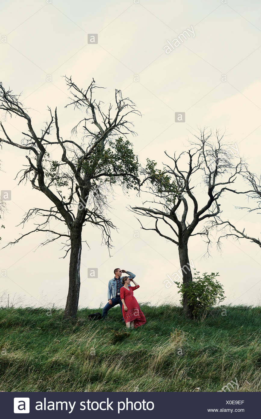 Pregnant couple looking out de hillside Photo Stock