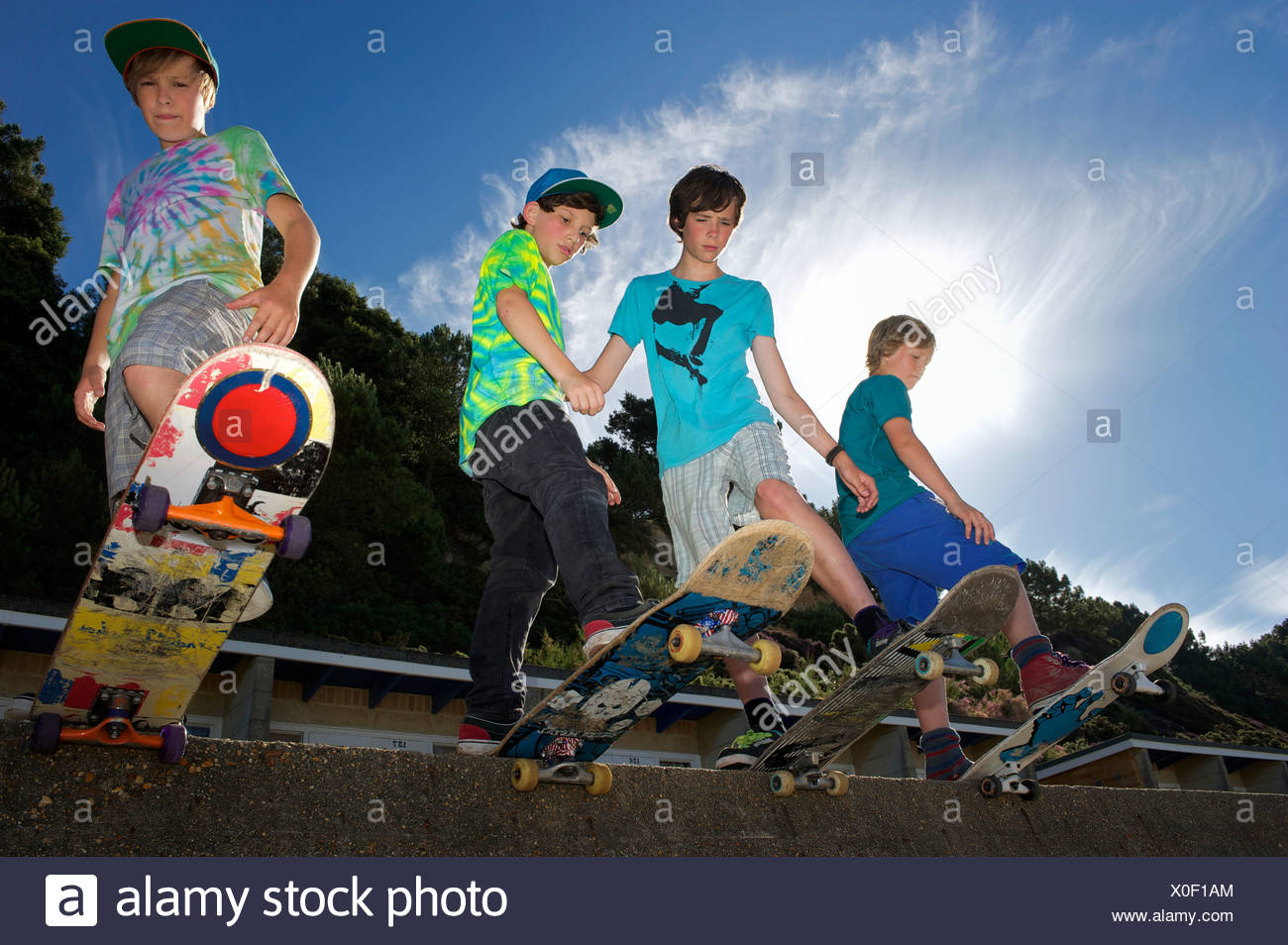 Portrait de quatre garçons sur skateboards Photo Stock