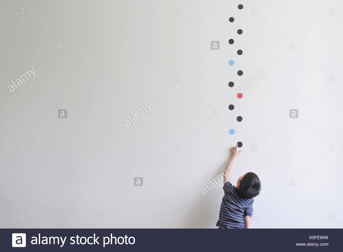 Garçon essaie de prendre l'un des motifs à points sur le mur Photo Stock