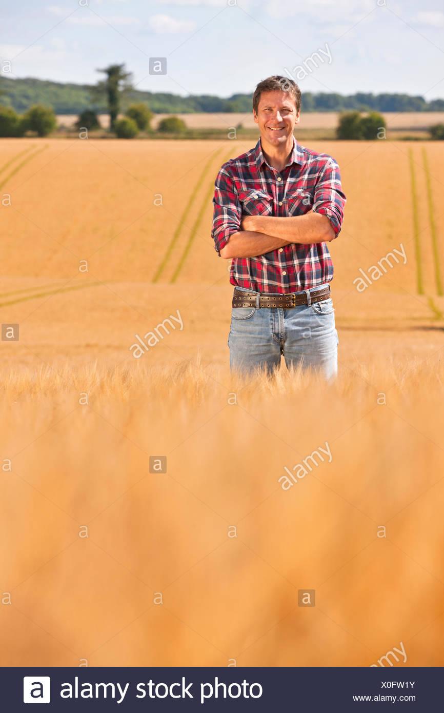 Portrait confiant farmer in rural crop field orge ensoleillée en été Photo Stock