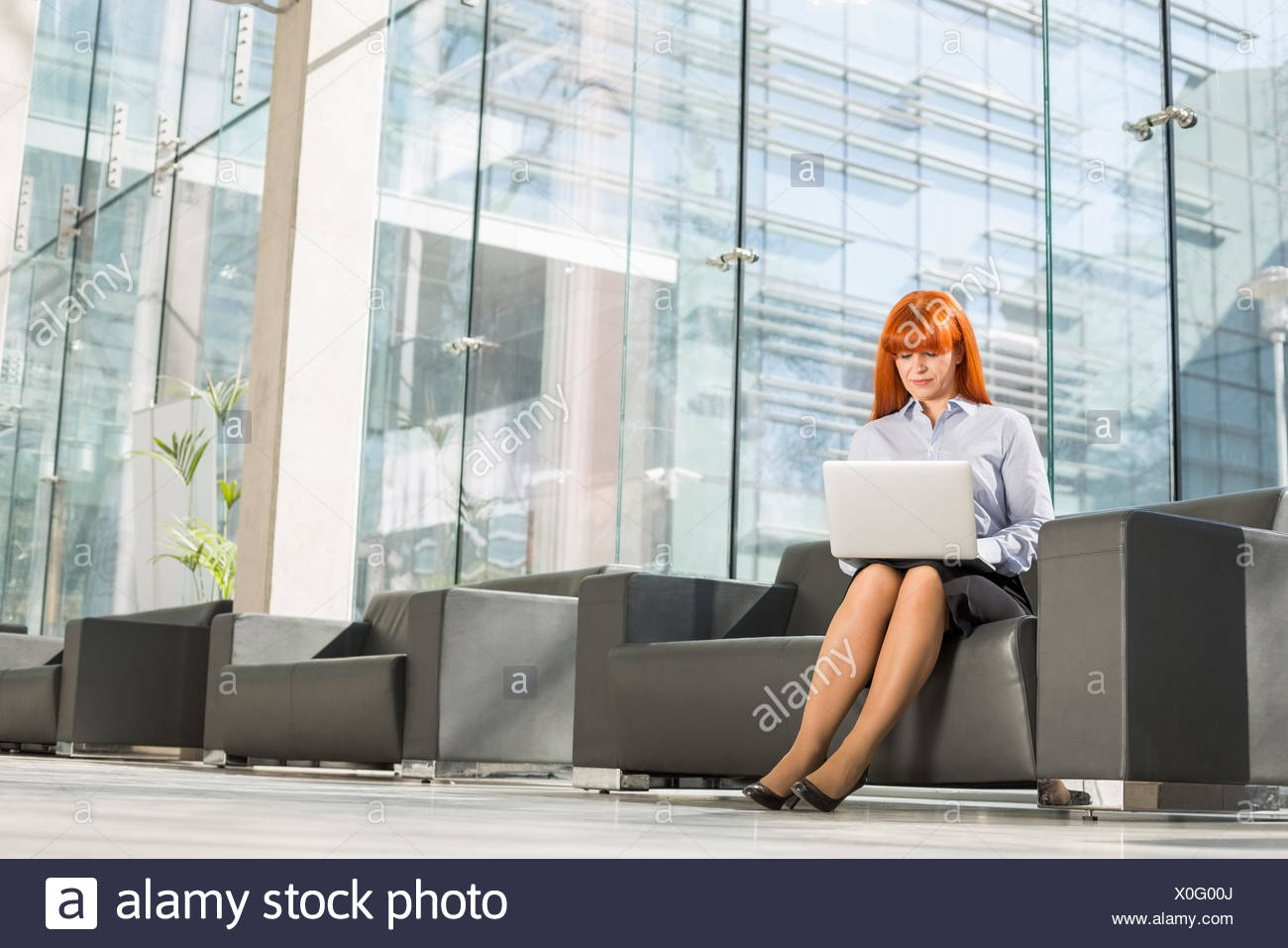 Full-length of middle-aged woman using laptop at office lobby Photo Stock