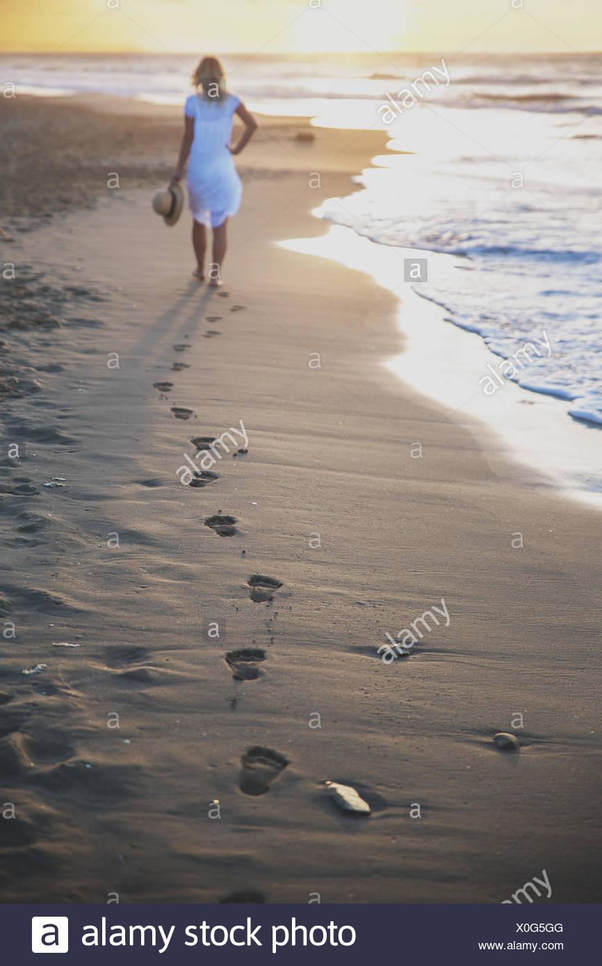 Belle femme marchant sur la plage avec ses empreintes de retour Photo Stock