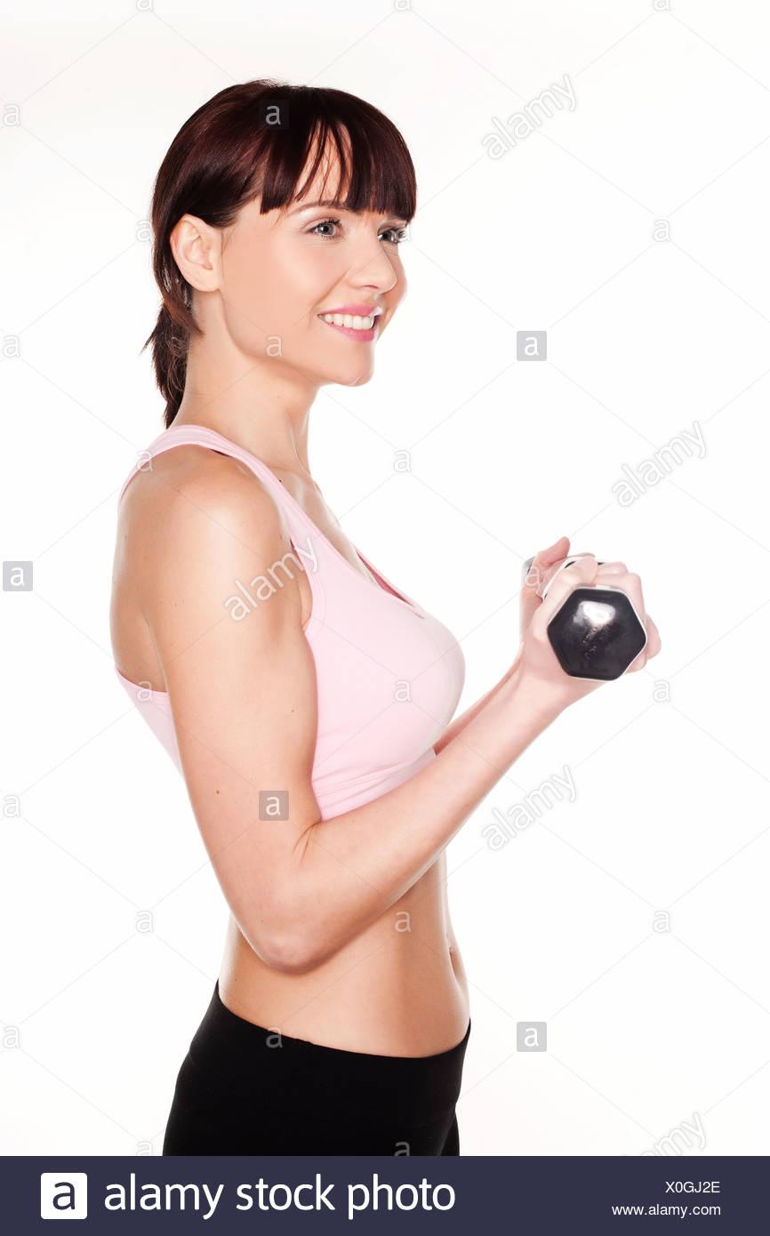 Profil de la partie supérieure du corps d'une jeune femme de la torsion d'un bras alors qu'elle élève tenant une haltère isolated on white Photo Stock