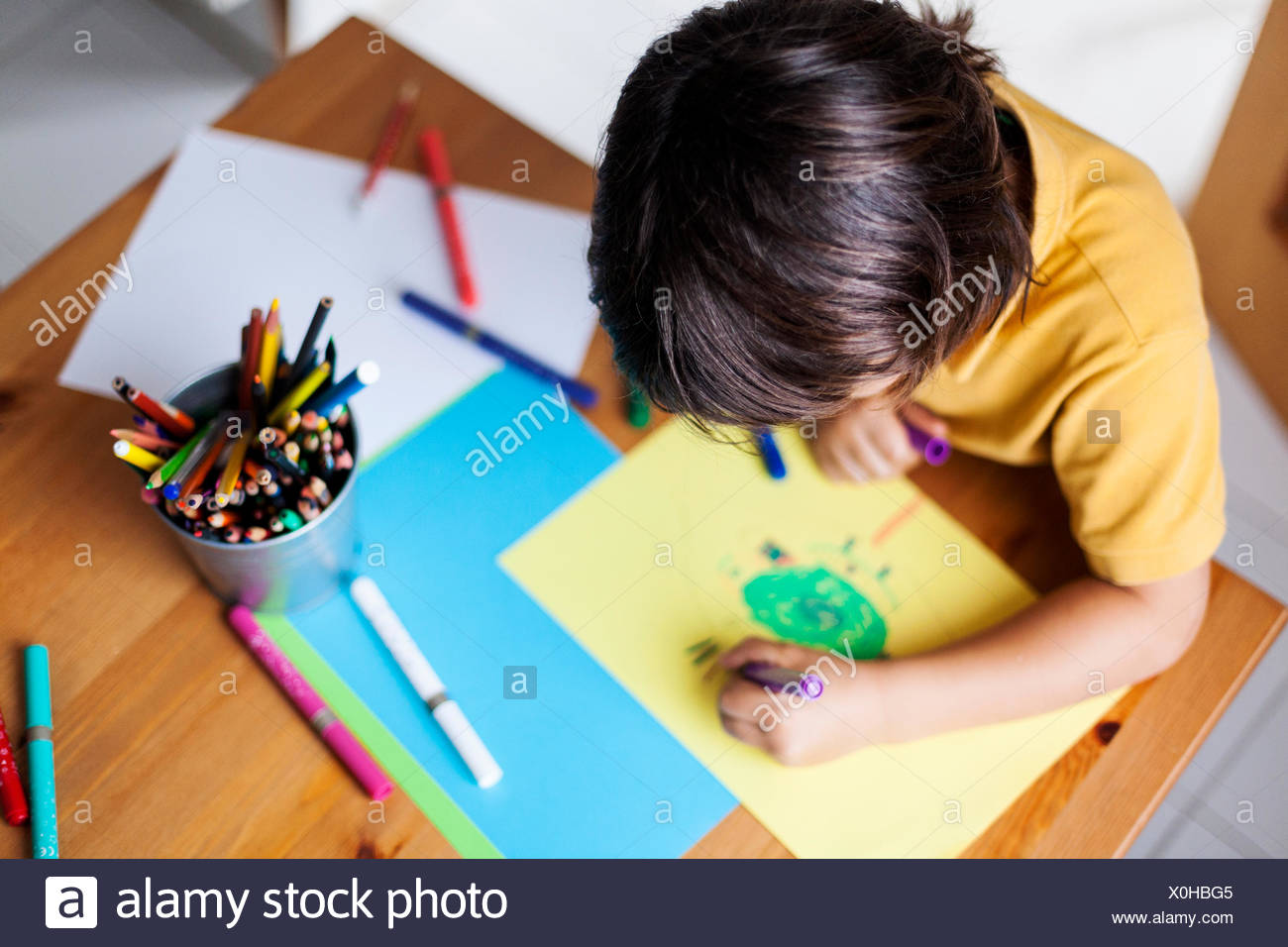 Petit garçon dessin sur papier jaune Photo Stock