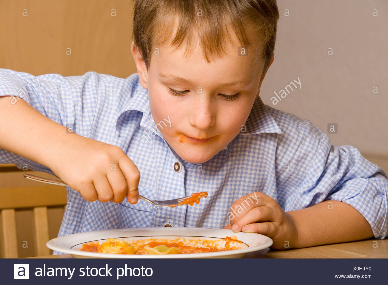 Portrait of young boy eating pasta Photo Stock