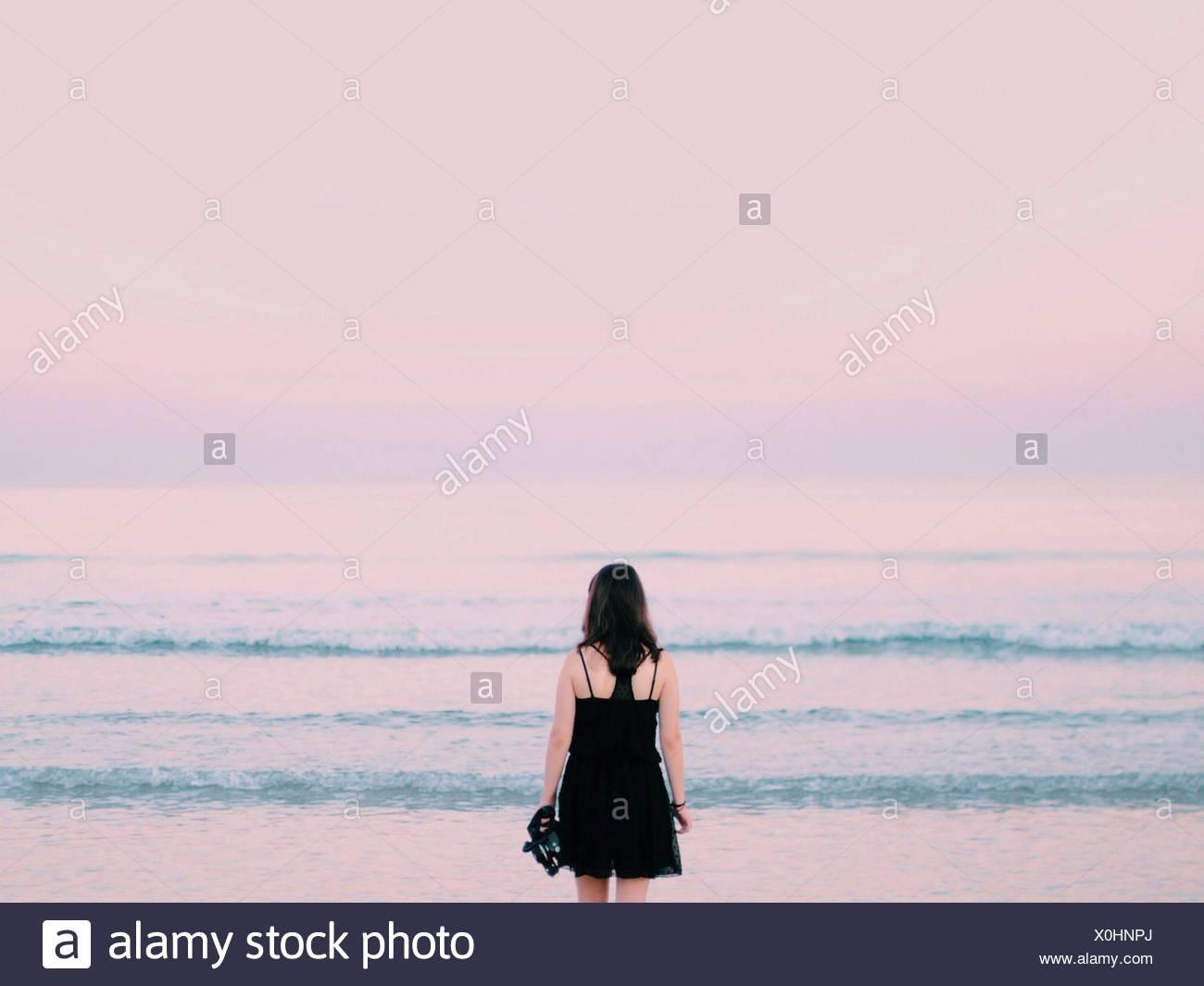 Vue arrière de la femme donnant sur une mer calme Photo Stock