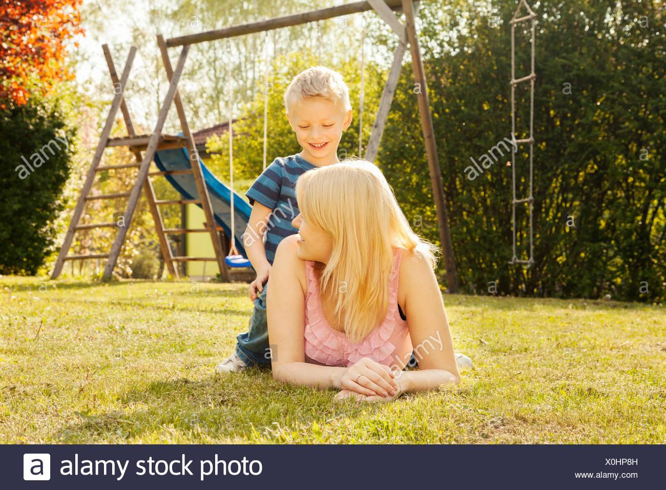 La mère et le fils dans le jardin, des balançoires en arrière-plan Photo Stock