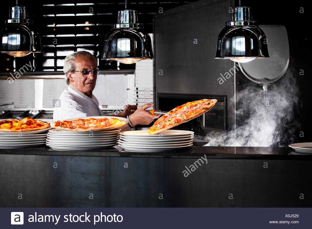 La prise de Baker Pizza pizza fini de sortir du four avec une pelle à pizza Banque D'Images