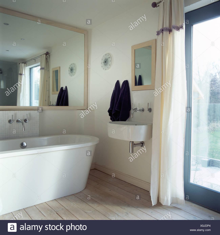 Grand Miroir Au Dessus De Baignoire Moderne Dans Petite Salle De Bains  Moderne Avec Lavabo Fixé Au Mur à Côté Du0027une Porte En Verre Avec Rideau  Blanc