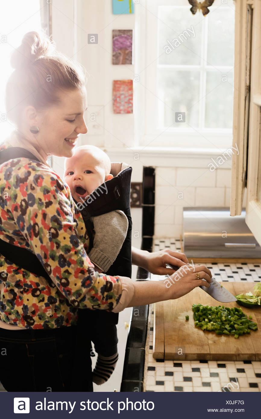 Mère de préparer des aliments adultes milieu avec bébé fils dans sling Photo Stock