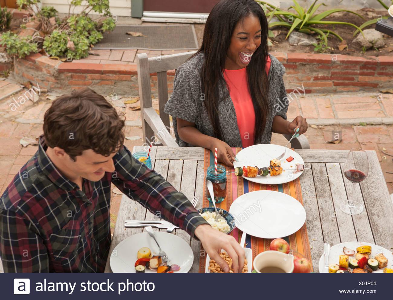 Amis assis autour de la table barbecue partage Photo Stock