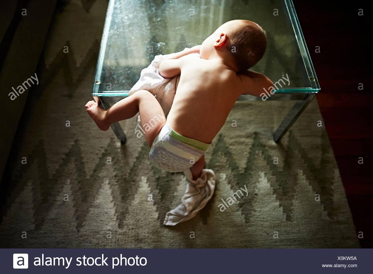 Demi-garçon grimper sur une table en verre Photo Stock