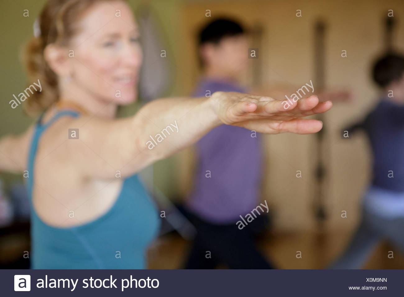 Femelle adulte avec les bras tendus et les doigts dans la classe d'exercice Photo Stock