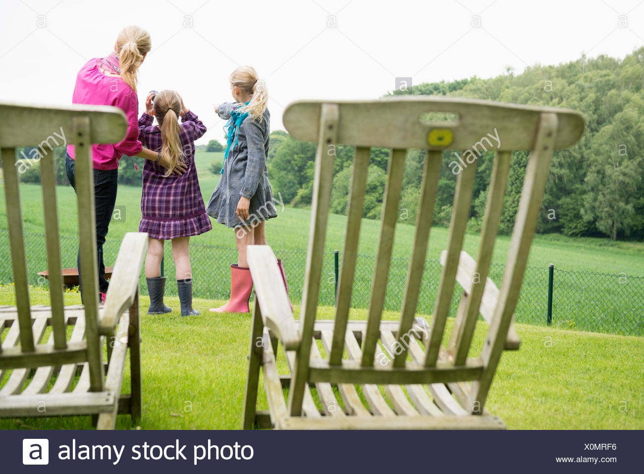 La mère et les filles à l'aide de jumelles, chaises en premier plan Photo Stock