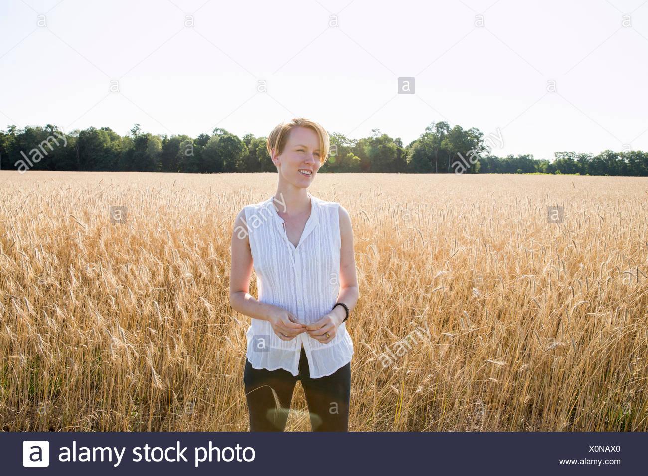 Demi-longueur portrait d'une jeune femme debout dans un champ de maïs. Photo Stock