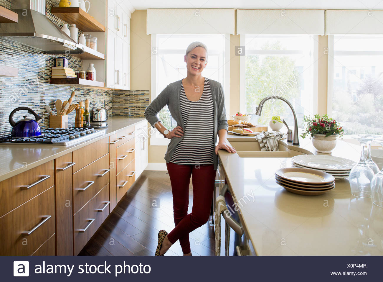 Portrait of smiling woman in kitchen Photo Stock