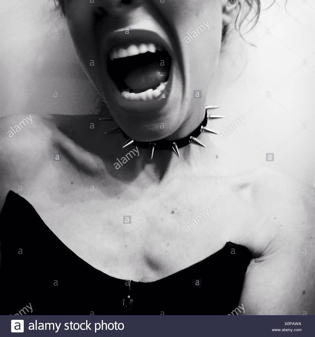 Portrait de jeune femme portant Collier avec pointes bouche ouverte contre fond blanc Photo Stock