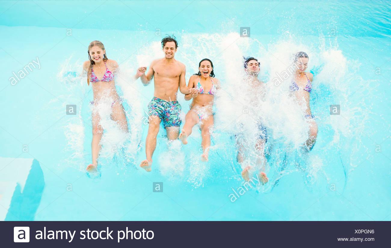 Les amis de sauter dans une piscine Photo Stock