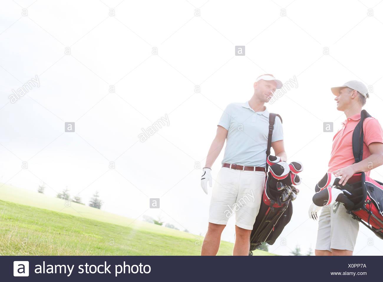 Amis de converser au golf contre ciel clair aux beaux jours Photo Stock