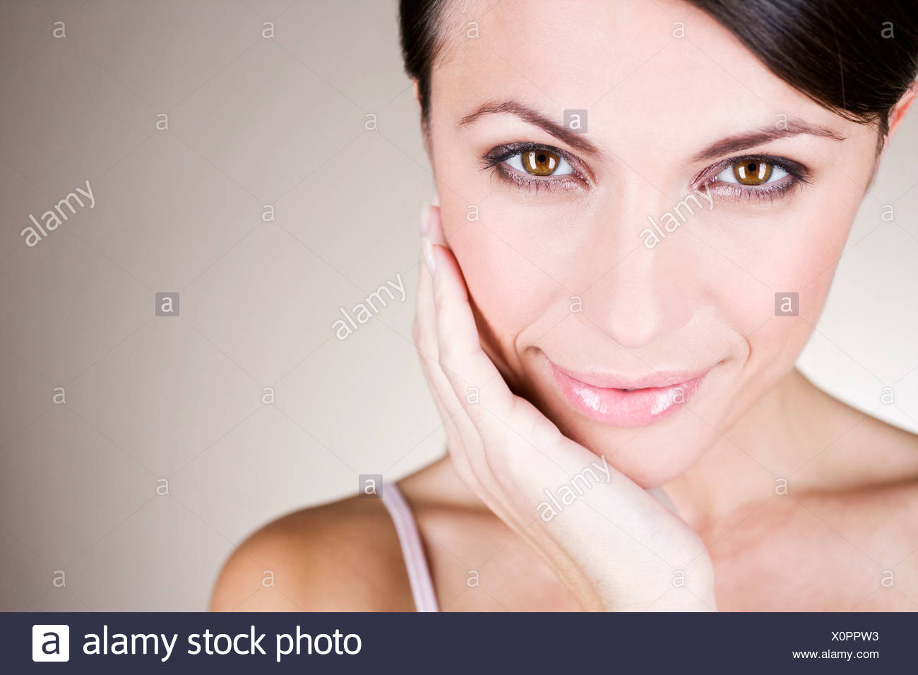 Portrait of a young woman touching her face Photo Stock