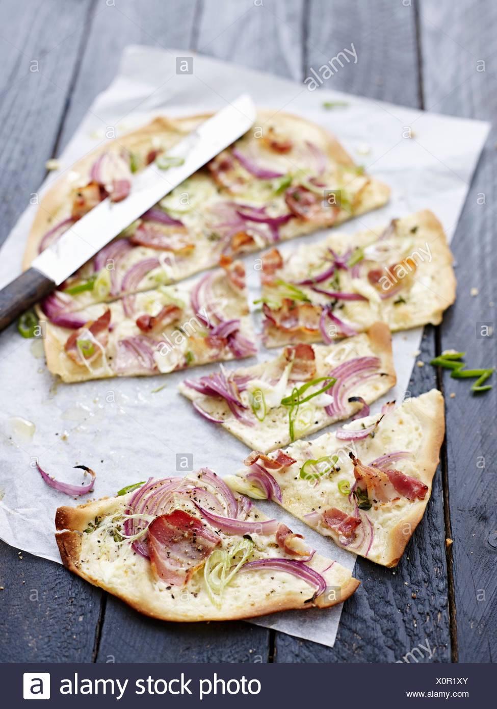 Tarte flambée avec oignons, oignons de printemps et du bacon Photo Stock
