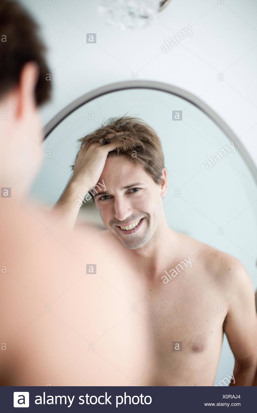 L'homme avec les mains dans les cheveux de se voir dans le miroir avec look d'amusement Photo Stock