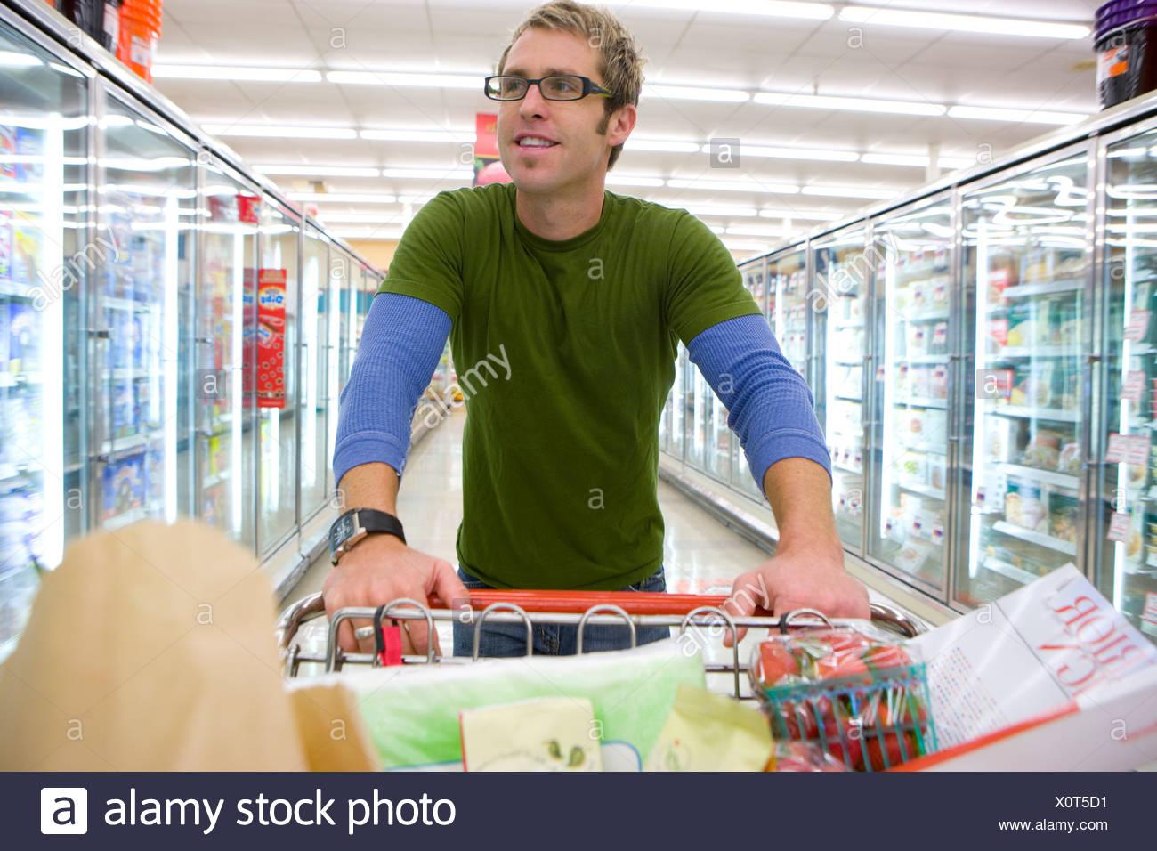 L'homme à l'épicerie dans la section des aliments congelés Photo Stock