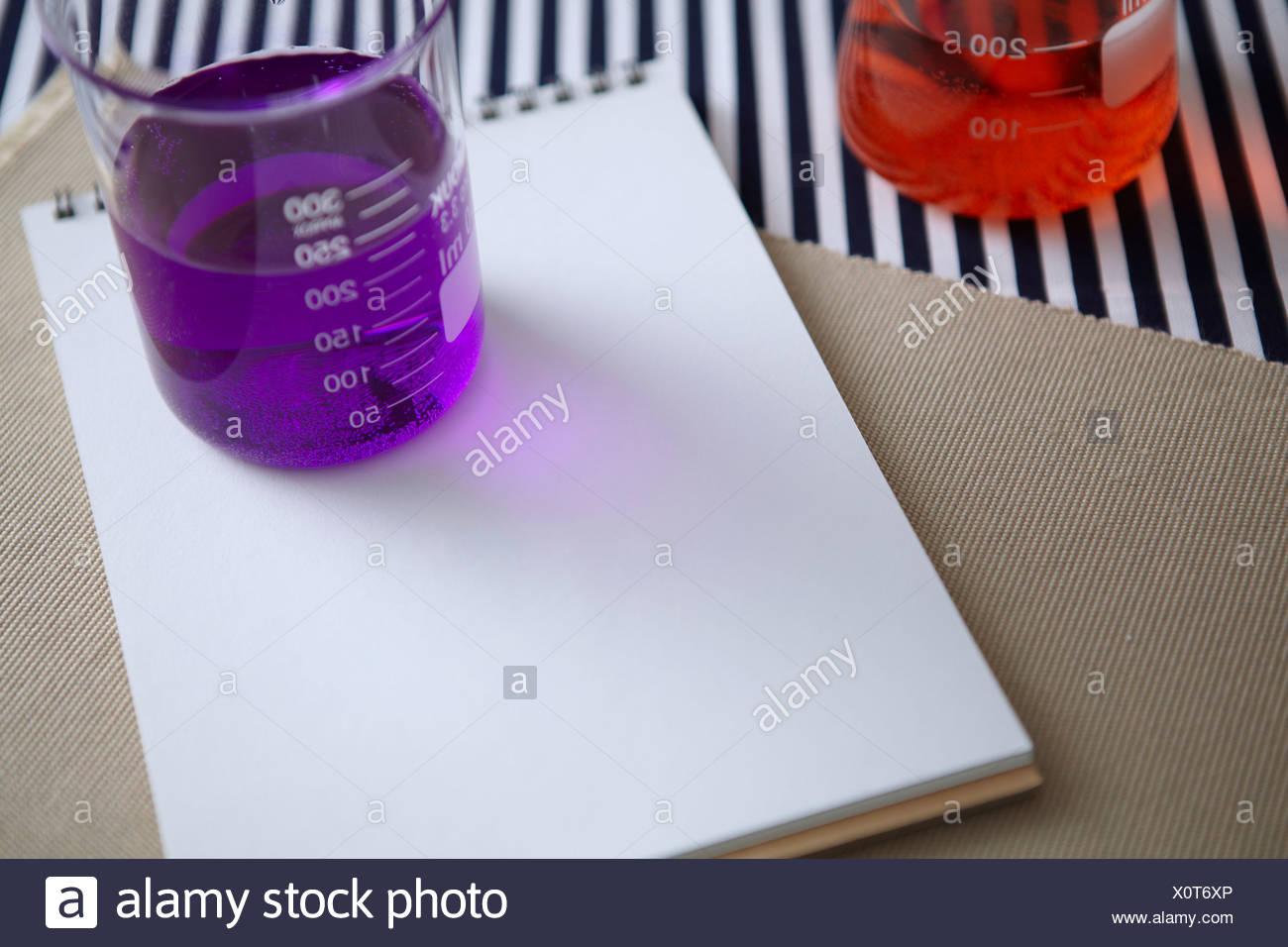 Verrerie de laboratoire avec le bloc-notes Banque D'Images
