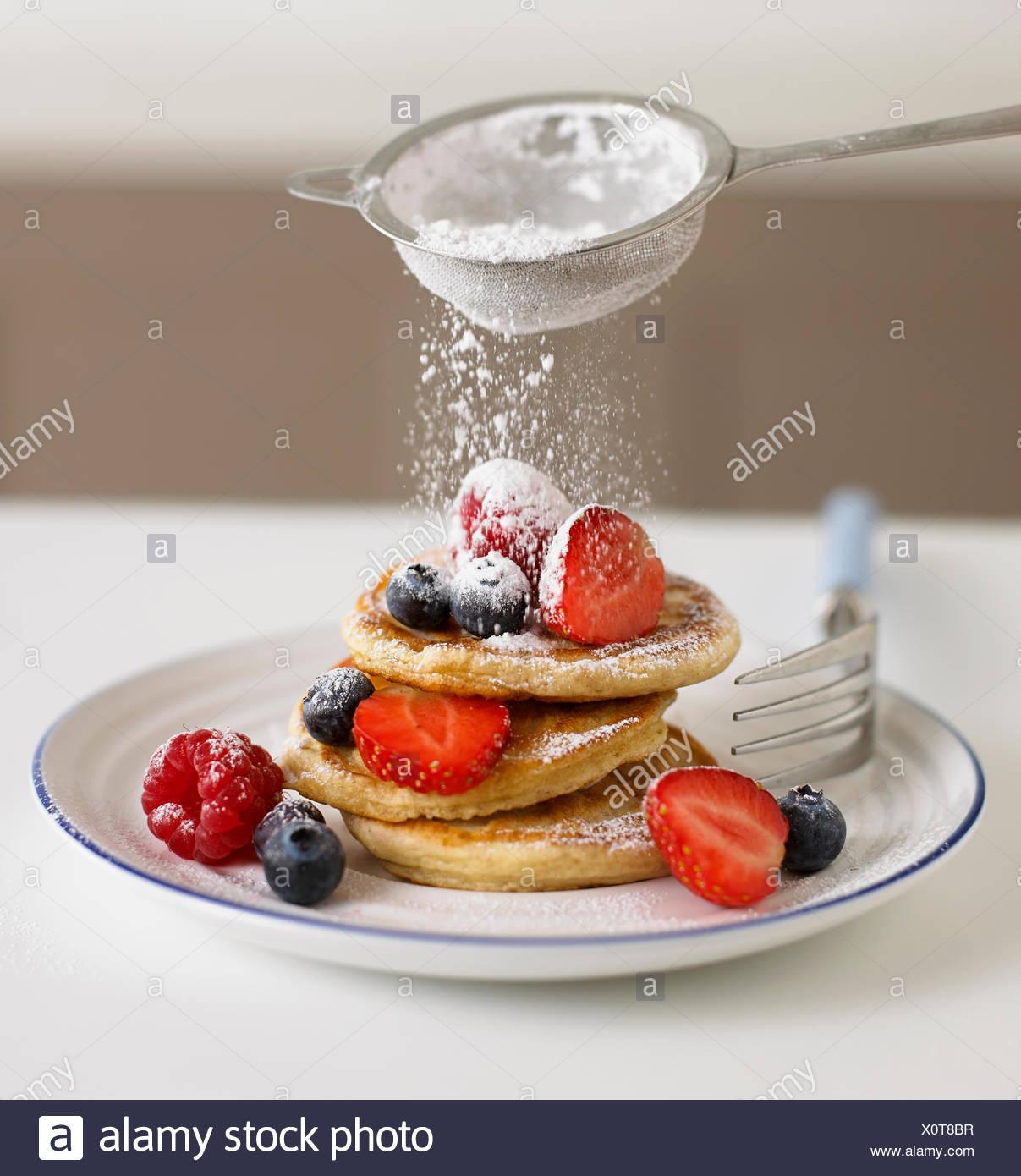 Tamiser le sucre à glacer sur fruits et crêpes Photo Stock