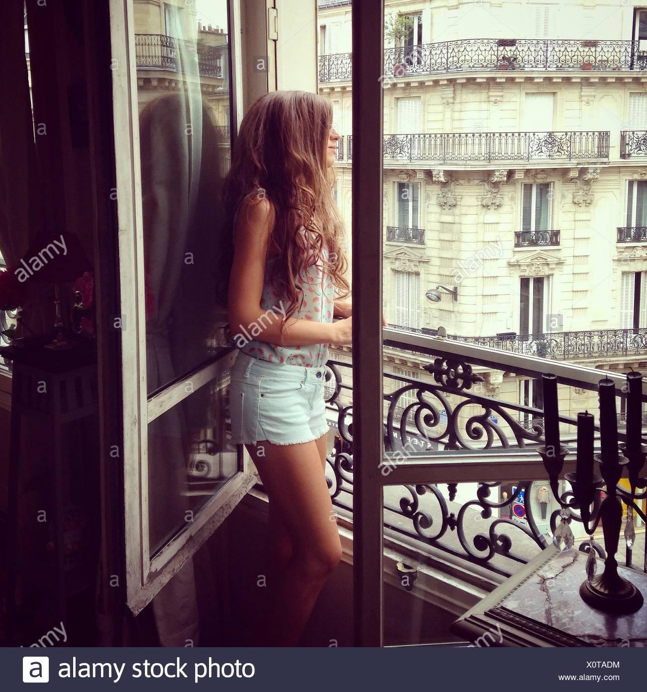Vue de côté de jeune femme à la recherche d'une fenêtre Photo Stock