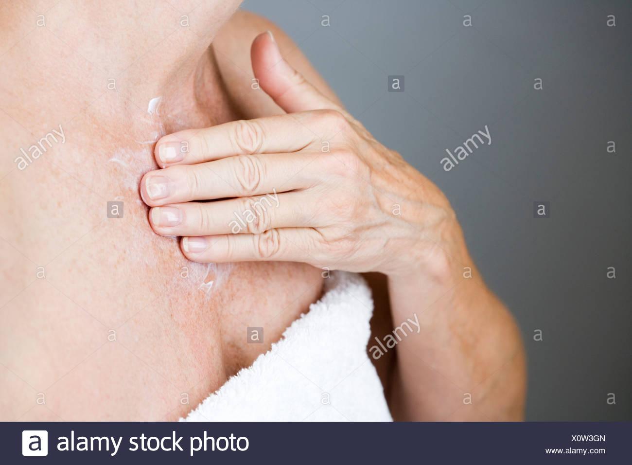 A l'application de la crème hydratante sur sa poitrine Photo Stock