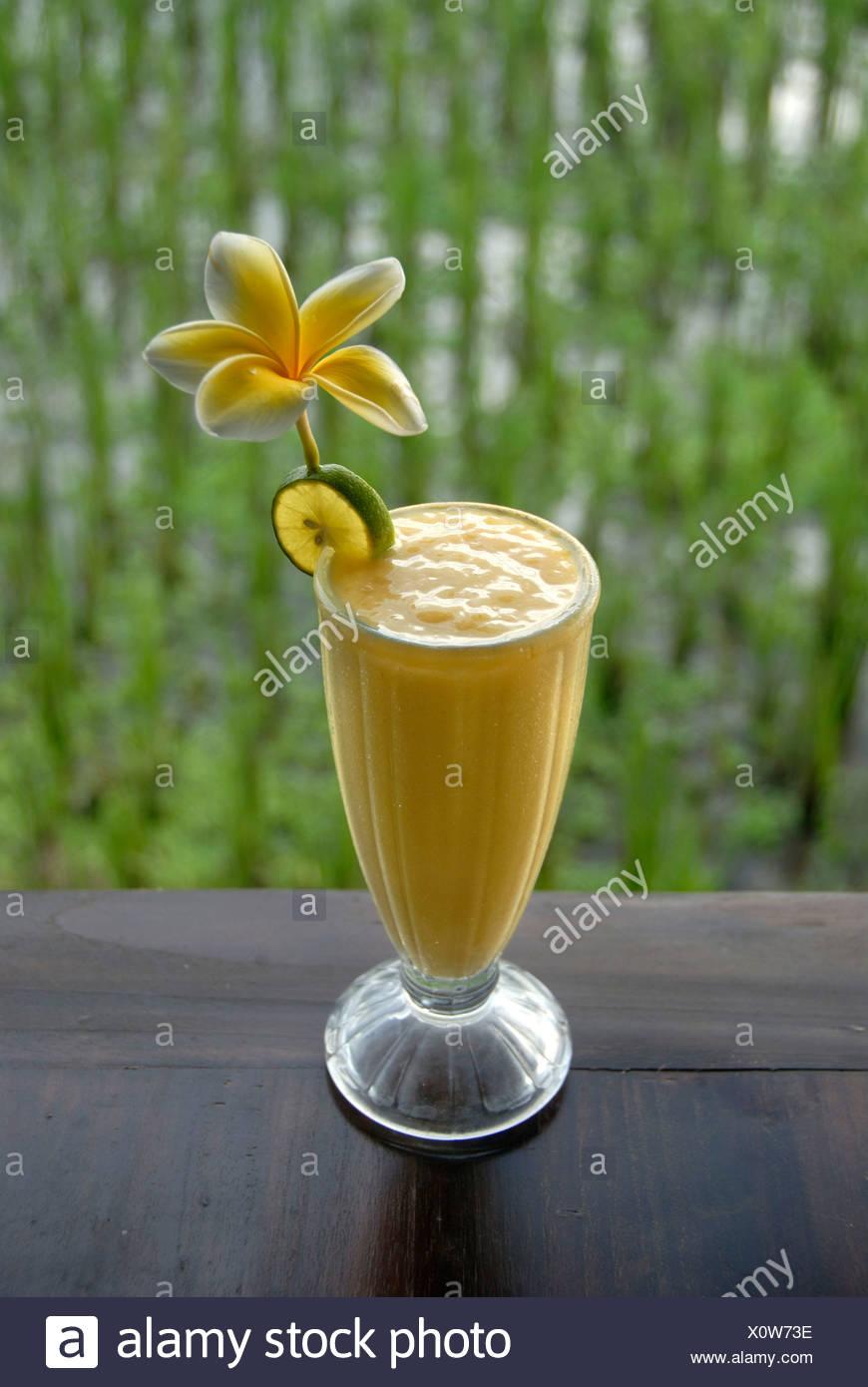 Smoothie à la mangue, boisson dans un verre décoré avec des fleurs, en face d'un champ de riz à Ubud, Bali, Indonésie, Asie du sud-est Photo Stock