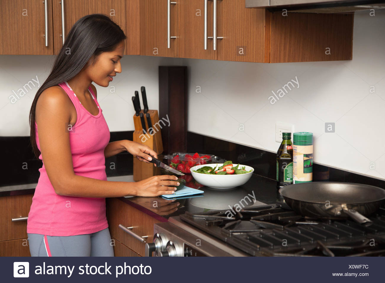 Woman preparing salad in kitchen Banque D'Images